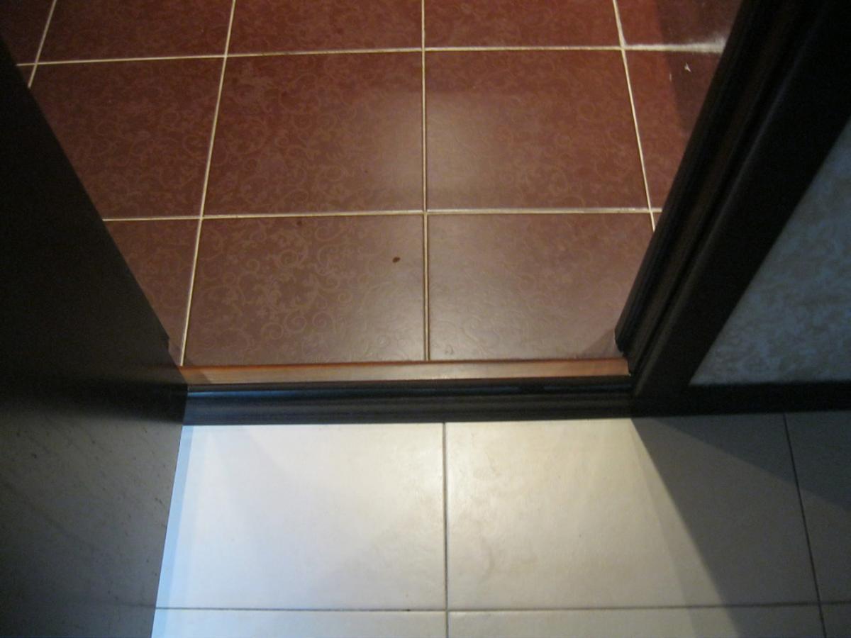 напольная плитка с порогом межу коридором и ванной