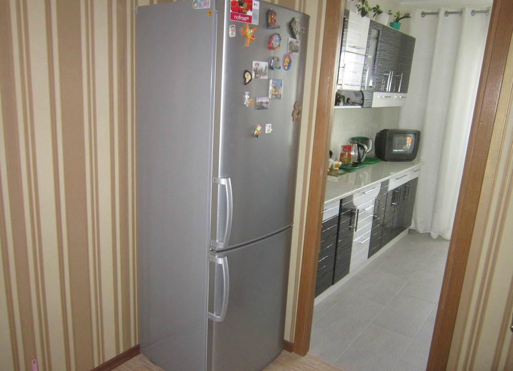 Холодильник стоящий у стены