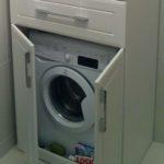 белая стиральная машинка в шкафу